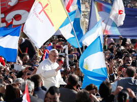 Flags from Argentina and other counties and movements are seen as Pope Francis greets the crowd before his Inaugural Mass.  CNS Photo/Paull Haring.