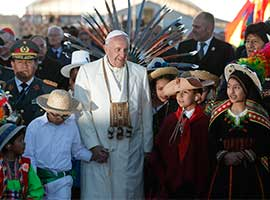 Pope Francis walks with Bolivian President Evo Morales and children in traditional dress as he arrives at El Alto International Airport in La Paz, Bolivia, in July 2015. CNS photo/Paul Haring