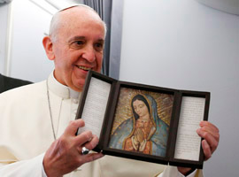 Pope Francis holds an image of Our Lady of Guadalupe after receiving it as a gift from a journalist aboard the papal flight to Brazil. (CNS photo/Paul Haring)