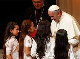 Pope Francis greets children during a meeting with representatives of civil society at the Leon Condou Stadium at St. Joseph's School in Asuncion, Paraguay, in July 2015. CNS photo/Paul Haring