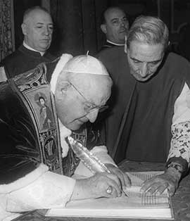 Pope John XXIII signs the bull convoking the Second Vatican Council Dec. 25, 1961. CNS photo.