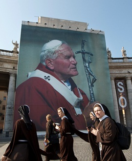 A group of nuns walks by a huge image of Blessed John Paull II displayed in St. Peter's Square at his beatification ceremony on May 1, 2011. CNS Photo/Paul Haring.