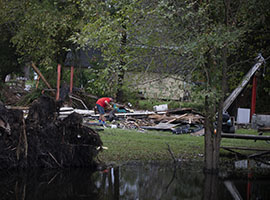 A man goes through the debris of his destroyed home in the aftermath of Hurricane Florence. (CNS photo/Bob Roller)
