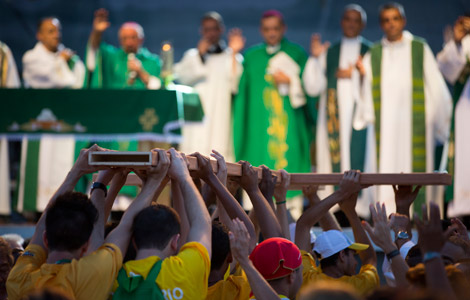 Pilgrims carry a cross to the altar during a Mass at the close of World Youth Day's missionary week in Nilopolis, Brazil. (CNS photo/Tyler Orsburn)