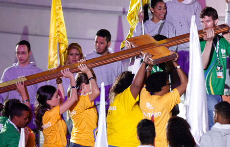 Young people carry the World Youth Day cross during the event's opening ceremony on Copacabana beach in Rio de Janeiro. (CNS photo/Paul Haring)