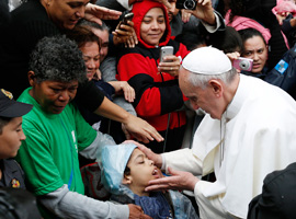 Pope Francis blesses a boy in the Varginha slum in Rio de Janeiro. (CNS photo/Paul Haring)