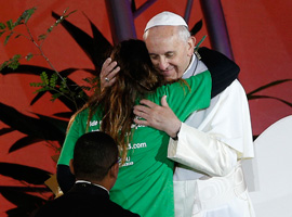 Pope Francis embraces a young woman during the World Youth Day welcoming  ceremony on Copacabana beach in Rio de Janeiro. (CNS photo/Paul Haring)