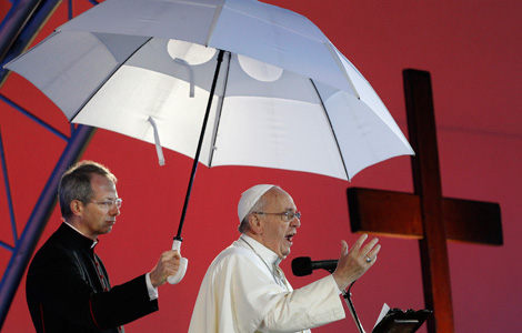 Msgr. Guido Marini, papal master of ceremonies, holds an umbrella for Pope Francis as he addresses World Youth Day Pilgrim. (CNS photo/Paul Haring)