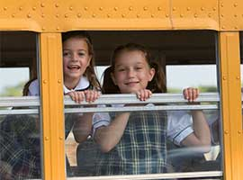 Two students looking out of school bus window. iStock Photo.