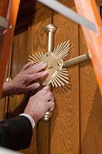 A worker places a gold cross on the Holy Door at the Basilica of the National Shrine of the Immaculate Conception in Washington, DC.  CNS photo/Matthew Barrick