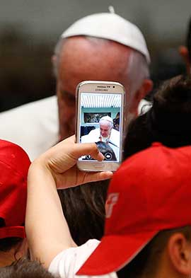 A youth takes a photo on a cell phone as Pope Francis meets children of Italian prisoners in Paul VI hall at the Vatican. CNS photo/Paul Haring
