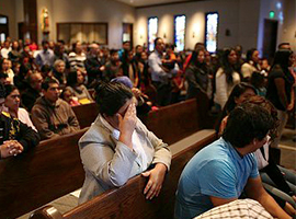A congregation in prayer at Mass. Corbis photo by Andrew Lichtenstein for illustrative purposes only.