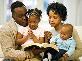 A young family reads the bible together.