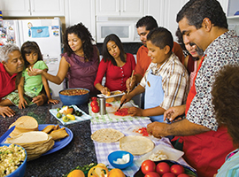 A Latino family prepares a meal together. Blend Images photo for illustrative purposes only.