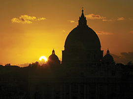 The dome of St. Peter's Basilica in Rome is illuminated at sunrise. iStock photo.