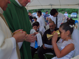 Girl receiving communion at Mass for migrants in the Diocese of Youngstown.