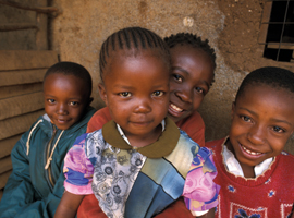 A group of young African children smiles for the camera.