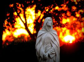 A statue of Mary is pictured against a vibrant late summer sunset Sept. 15 on the grounds of St. Mary Catholic Cemetery in Menasha, Wis. Fall arrives Sept. 23. (CNS photo/Brad Birkholz