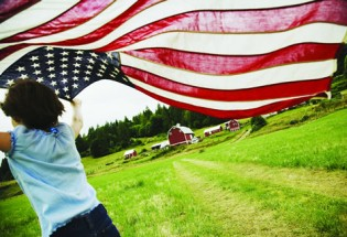 girl runs by barn with American flag home