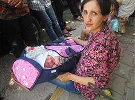 An Iraqi Christian refugee holds a  newborn baby in Ankawa Iraq in August 2014. CNS photo/Sahar Mansour