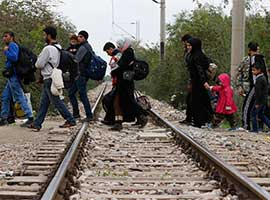 Refugees cross train tracks into Macedonia after arriving at transit camp in Idomeni, Greece. CNS Photo/Paul Haring