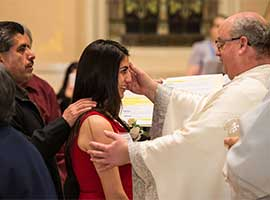 Norbertine Father Andrew Cribben, pastor of St. Willebrord Church in Green Bay, Wis., places sacred chrism oil on the forehead of Nahidaly Fiscal during the a 2014 Easter Vigil. CNS photo/Sam Lucero, The Compass