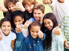 group of children giving thumbs up signal