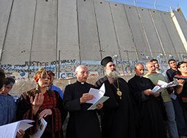 Christian leaders pray in front of the Israeli separation wall in Bethlehem, West Bank, in 2010. CNS photo/Debbie Hill