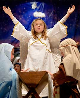 The Nativity angel, played by second-grader Sarah Glazier, visits Mary and Joseph at the end of