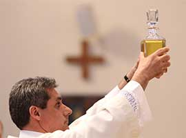 Deacon Raymond D'Alessio of St. Edward the Confessor Parish in Syosset, N.Y., holds a decanter containing the oil of the sick during the annual chrism Mass at St. Agnes Cathedral in Rockville Centre, N.Y., in 2014. CNS photo/Gregory A. Shemitz