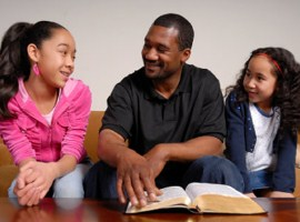 A father studies the bible with his two daughters.