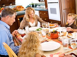 A family joins hands in prayer before their meal. iStock image used for illustrative purposes only.
