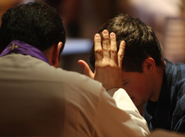 A young penitent receives absolution. CNS Photo/Gregory A. Shemitz