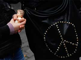 A woman holds a figurine of the baby Jesus next to a purse with the peace symbol in St. Peter's Square. CNS photo/Paul Haring