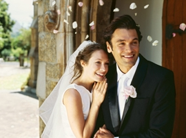 A bride and groom smile outside of a church. Getty image for illustrative purposes only.
