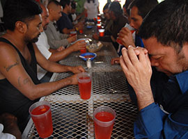 Migrants pray before breakfast at a dining facility in Nogales, Mexico, that is supported by the Jesuit-run Kino Border Initiative. CNS photo/David Maung