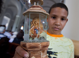 A young Cuban boy holds up his statue of the Virgin of El Cobre the patroness of Cuba. CNS Photo/Nancy Phelan Wiechec.