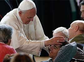 Pope Francis blesses a man while greeting the disabled at Queen of Peace Parish in Ostia on the outskirts of Rome. CNS photo/Paul Haring