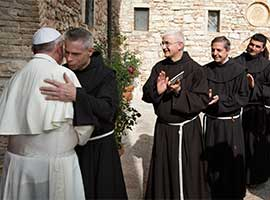 Franciscan Father Michael Perry embraces Pope Francis during his visit to the hermitage  of Saint Francis in October 2013.