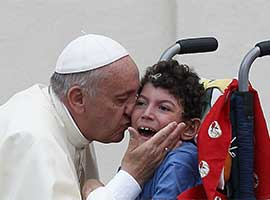 Pope Francis kisses a disabled child. CNS Photo/Paul Haring.