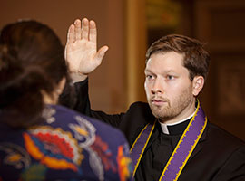 Fr. Kevin Regan of the Archdiocese of Washington demonstrates the granting of absolution during the sacrament of reconciliation. (CNS photo/Nancy Phelan Wiechec