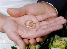 A bride and groom hold their wedding rings as they are blessed.  iStock photo