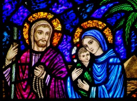 A detail of a stained-glass window from St. Edward's Church in Seattle shows Jesus, Mary and Joseph on their flight into Egypt. CNS Photo/Crosiers