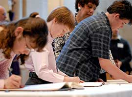Young people sign the Book of the Elect during a 2009 Rite of Election ceremony for catechumens and candidates at Sacred Heart Cathedral in Rochester, N.Y.  CNS photo/Mike Crupi, Catholic Courier