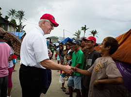 Archbishop Joseph E. Kurtz, president of the U.S. Conference of Catholic Bishops, greets a line of Filipinos in Anibong, a community in Tacloban, Philippines in February 2014. CNS photo/Tyler Orsburn