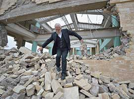 Father Emanuel Youkhana, an archimandrite of the Assyrian Church of the East, walks through the rubble of a demolished church in Mosul, Iraq, in January 2017. (CNS photo/Paul Jeffrey