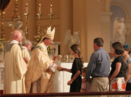 Archbishop William E. Lori greets a member of the congregation at the 2014 Closing Mass for the Fortnight for Freedom.