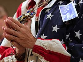 closing-mass-2014-attendee-rosary-flag-jacket-cns-montage