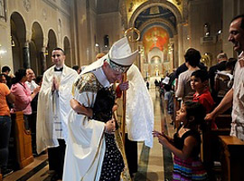A young girl embraces Cardinal Donald Wuerl of Washington during the recessional of the Fortnight for Freedom closing Mass at the Basilica of the National Shrine of the Immaculate Conception in Washington, DC on July 4. (CNS photo/Leslie E. Kossoff)