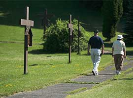A couple walks a path lined with the Stations of the Cross at the National Shrine of Blessed Kateri Tekakwitha in Fonda, N.Y. CNS photo/Nancy Wiechec